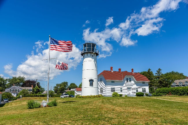 The lighthouse of Chatham and the american flag waving